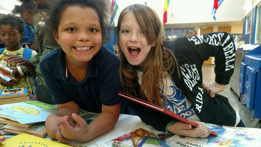 Two girls smiling with books from the Cleveland Kids' Book Bank at their after school arts program