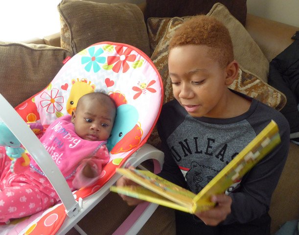 Boy reading book from the Cleveland Kids' Book Bank to his baby sister
