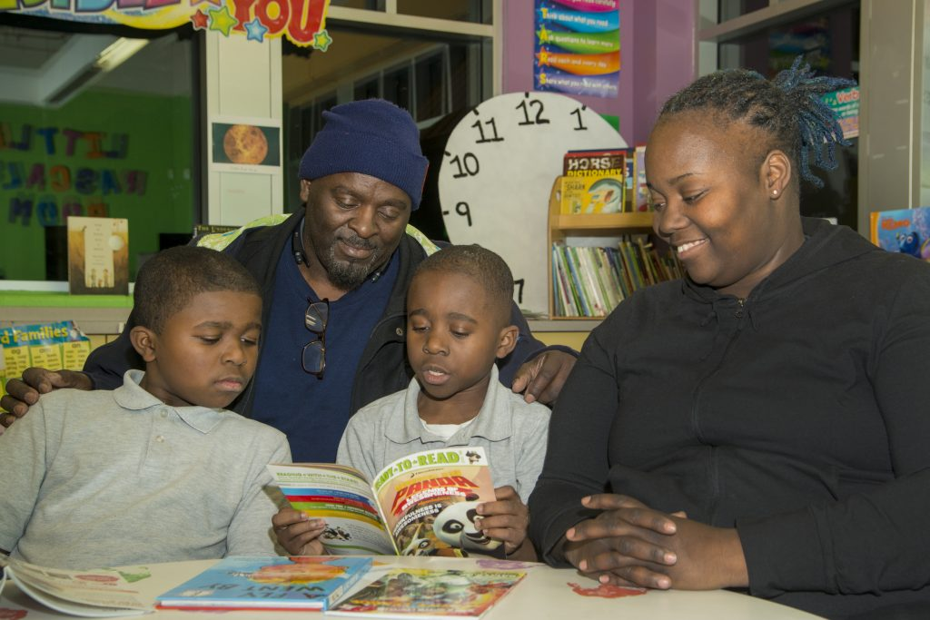 Family reading books from Cleveland Kids' Book Bank together at Cleveland Boys & Girls Club