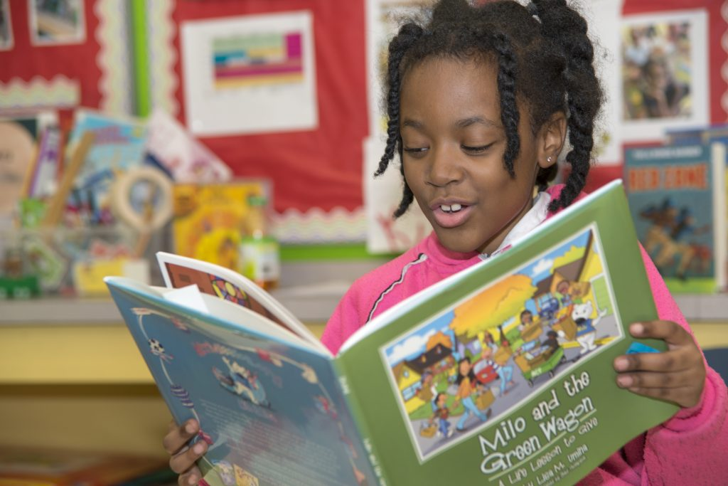 Girl reading a book from the Cleveland Kids' Book Bank