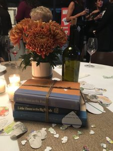 Flower vase on top of books centerpiece at Cleveland Kids' Book Bank Eat, Drink, & Be Literary! event