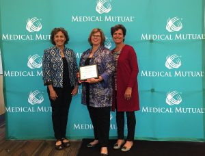 Judy Payne, Ellen Mattingly, and Judi Kovach pose in front of the Medical Mutual banner