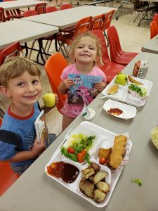 Boy and girl at a cafeteria table smiling at the camera