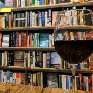 Glass of wine in front a bookcase for Cleveland Kids' Book Bank fundraiser
