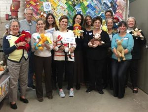 SVP Cleveland partners pose in front of the book wall at the Kids' Book Bank after volunteering sorting and packing books
