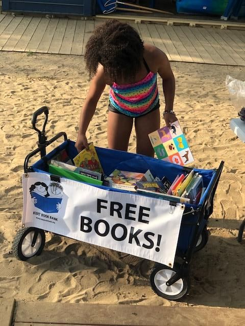 Girl in striped swimsuit selecting books from the Cleveland Kids' Book Bank wagon