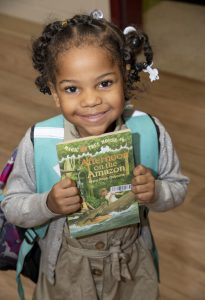 Hazel holding the Magic Tree House book from the Cleveland Kids' Book Bank