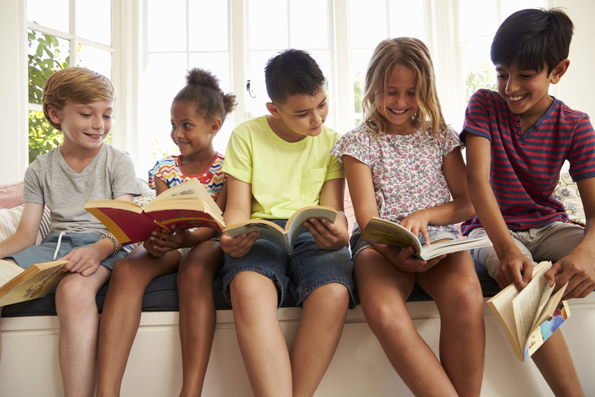 photo of kids sitting in front of window reading
