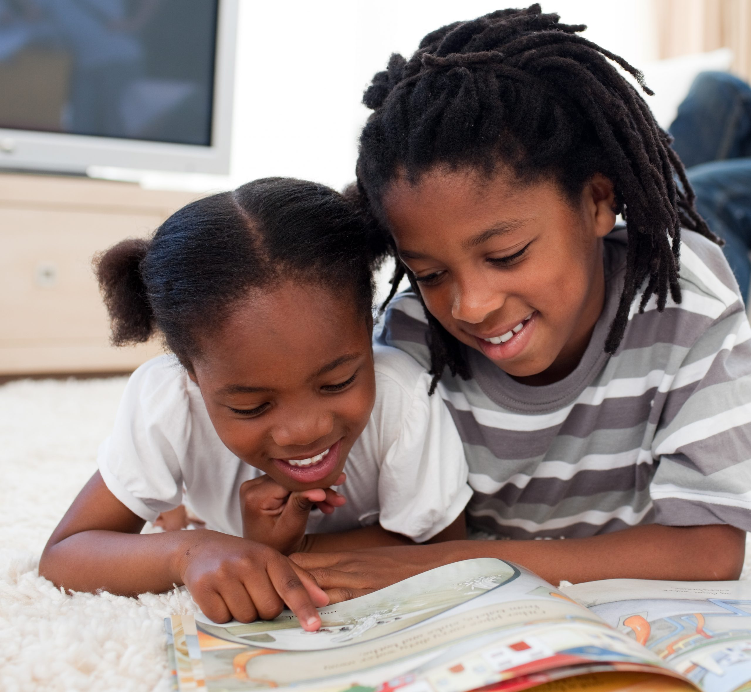 boy and girl laying on floor reading a book and smiling