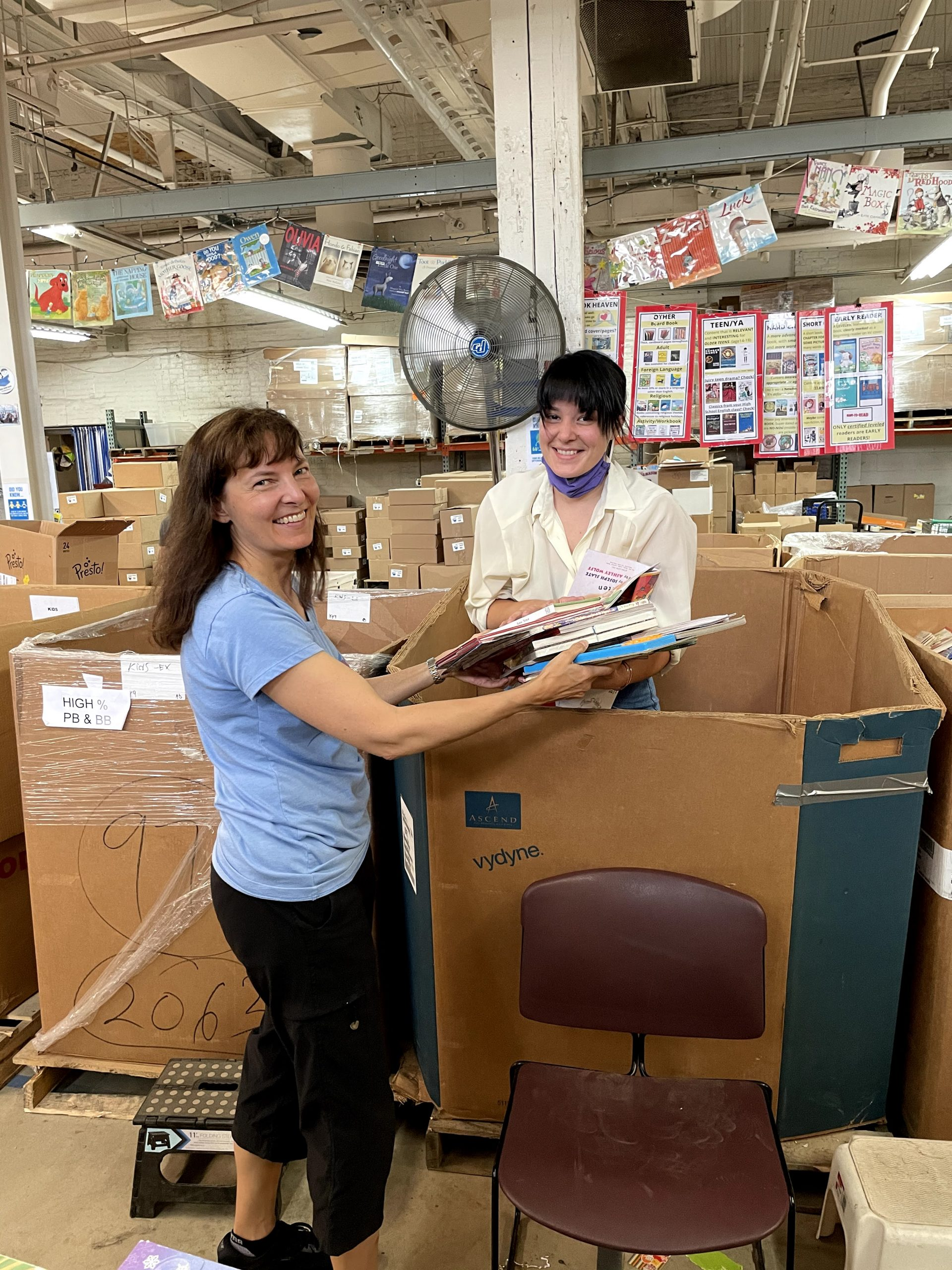 Two volunteers sort books from a gaylord in the Cleveland Kids' Book Bank warehouse