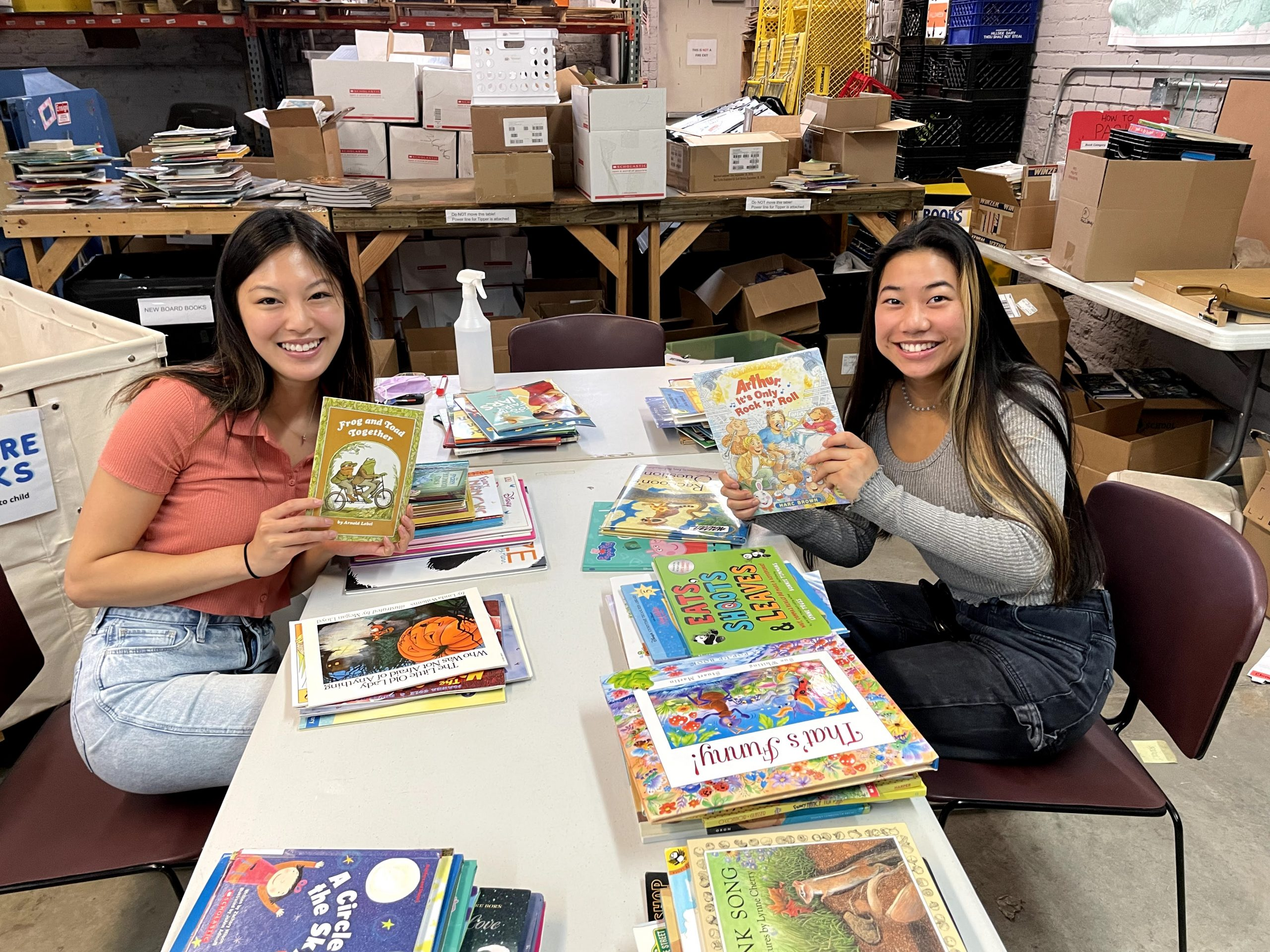 Two smiling young women seated at a table of books at the Cleveland Kids' Book Bank warehouse