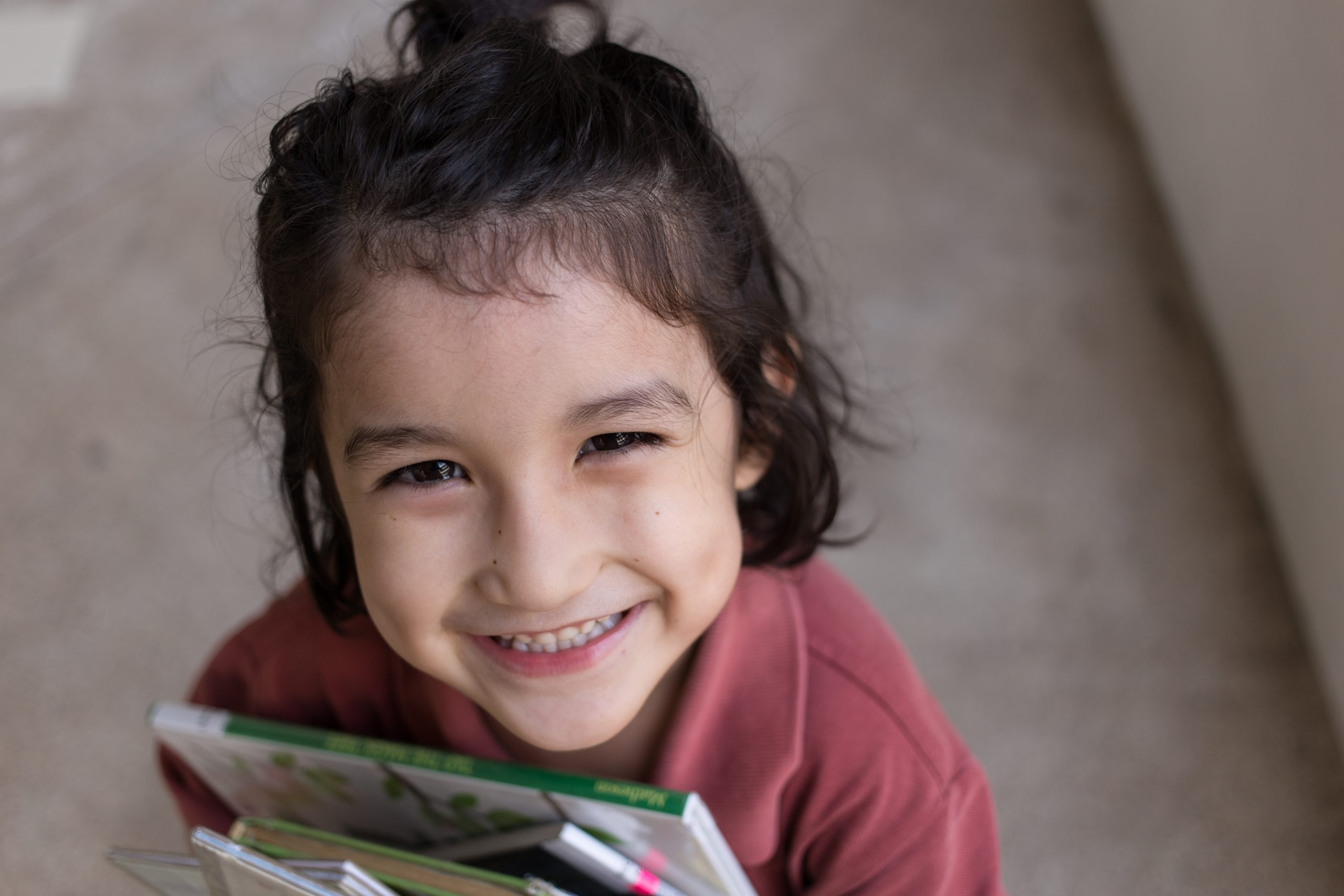 young girl with dark hair holding books and smiling